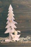 欢乐装饰圣诞树和一个玩具天使在木背景在葡萄酒颜色 免版税库存图片