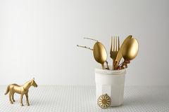欢乐金黄利器刀子和叉子匙子在一个白色瓶,轻的背景 图库摄影