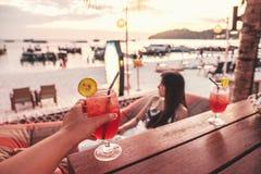 欢呼与在海滩党夏天概念的热带鸡尾酒的愉快的朋友 库存图片