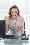 欢呼与握紧拳头的女实业家在办公室 免版税图库摄影