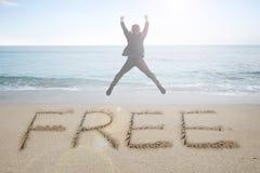 欢呼与自由词的跳跃的商人手写在沙子 免版税库存图片
