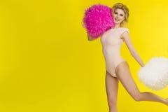 欢呼与pom pom,黄色背景的愉快的白肤金发的女孩 免版税库存图片