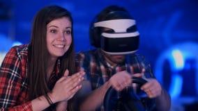 欢呼为她的男朋友的愉快的女朋友使用赛跑在虚拟现实耳机的计算机游戏 免版税图库摄影