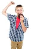 欢呼和享用choco筹码曲奇饼的男孩 免版税图库摄影