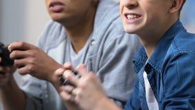 欢呼和庆祝获胜在电子游戏,喜爱的爱好中的两个年轻朋友 影视素材