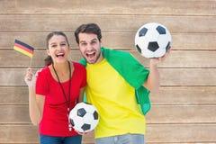 欢呼和微笑对照相机的足球迷夫妇的综合图象 图库摄影