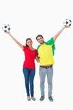 欢呼和微笑对照相机的足球迷夫妇 免版税图库摄影