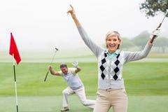 欢呼在与后边伙伴的照相机的夫人高尔夫球运动员 库存照片