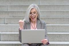 欢呼在喜讯的欢腾的女实业家 免版税库存图片