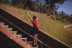 欢呼在楼梯的愉快的女孩在障碍桩期间 库存照片