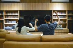 欢呼在电视前面的亚洲夫妇在客厅在晚上 免版税图库摄影