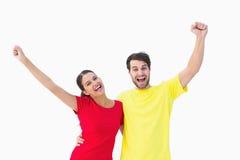欢呼在红色和黄色T恤杉的激动的夫妇 免版税库存图片