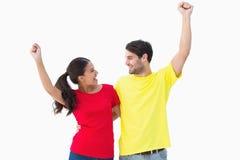 欢呼在红色和黄色T恤杉的激动的夫妇 图库摄影