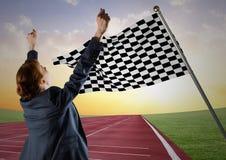 欢呼在轨道反对方格的旗子和平衡天空的女商人 库存照片