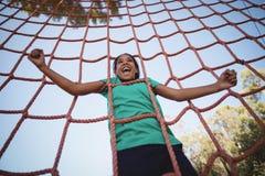 欢呼愉快的女孩,当攀登网在障碍桩期间时 图库摄影
