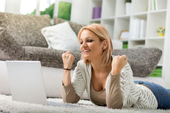 欢呼愉快的女孩,当看膝上型计算机时 免版税库存照片