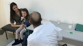 欢呼有兔宝宝玩具的小女孩患者的儿科医生医生 免版税库存图片