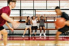 欢呼男孩的十几岁的女孩打篮球 免版税库存照片