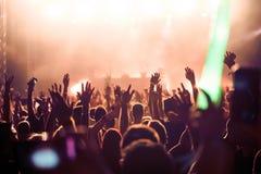 欢呼的人群用在空气的手在音乐节 免版税库存图片