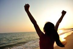 欢呼的妇女对日出张开胳膊海上 免版税库存图片