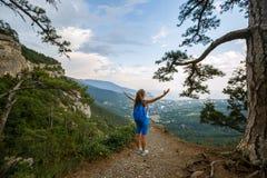 欢呼的妇女远足者打开胳膊在山峰,充满喜悦的女孩传播的与背包的手和启发  库存图片