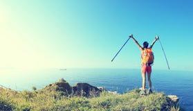欢呼的少妇远足者张开在海边山的胳膊 免版税库存图片