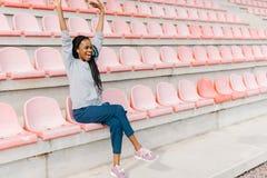 欢呼的美国黑人的妇女观看在体育场的比赛 免版税库存照片