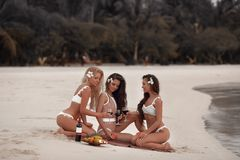 欢呼!呼吁三个性感的比基尼泳装女孩室外照片喝酒在热带海滩的一顿野餐期间在马尔代夫海岛 亭亭玉立 免版税库存图片
