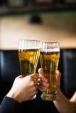 欢呼 衬衣的敬酒用啤酒的两个人特写镜头在酒吧柜台 免版税图库摄影