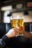 欢呼 衬衣的敬酒用啤酒的两个人特写镜头在酒吧柜台 免版税库存图片