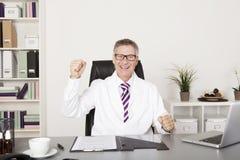 欢腾的医生坐的欢呼在他的办公室 免版税库存照片