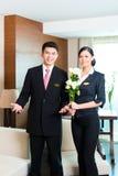 欢迎亚裔中国的旅馆经理VIP客人 免版税库存照片