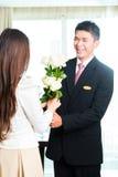 欢迎亚裔中国的旅馆经理VIP客人 免版税图库摄影