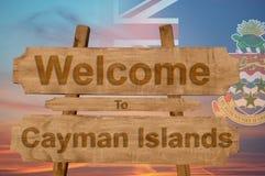 欢迎光临开曼群岛在与混和国旗的木背景唱歌 免版税库存图片