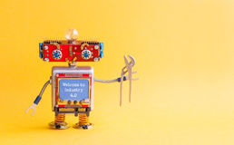 欢迎到产业4 红颜色的词位于在白色颜色文本 IT专家steampunk机械机器人,兴高采烈的红色头,蓝色显示器身体,钳子 免版税库存照片