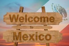 欢迎到在木背景的墨西哥标志与混和国旗 图库摄影