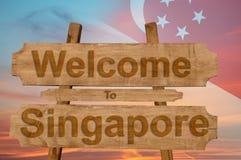欢迎到在木背景的新加坡标志与混和国旗 免版税库存照片