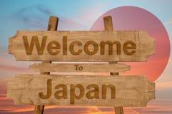 欢迎到在木背景的日本标志与混和国旗 免版税库存照片