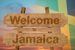欢迎到在木背景的牙买加标志与混和国旗 免版税库存照片