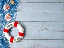 欢迎在船上- lifebuoy与文本和壳在木背景 库存照片