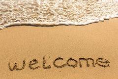 欢迎-在沙子海滩的题字 免版税库存照片