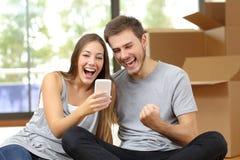 欣快夫妇移动的房子和观看的电话 免版税库存照片