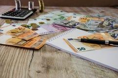 欧元、美元、硬币、笔记本、笔和计算器在木背景关闭 免版税库存照片