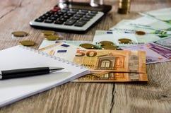 欧元、美元、硬币、笔记本、笔和计算器在木背景关闭 库存图片