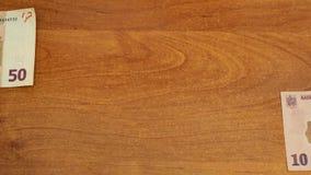 欧元和列伊的停止运动动画在木书桌上 影视素材