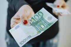 100欧元在妇女` s手和钱包上 免版税库存图片