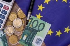 100欧元撕毁与硬币、笔和计算器在桌上 免版税库存照片