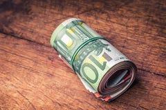 欧元注意反映 钞票概念性货币欧元五十五十 开户欧洲欧元五重点一百货币附注绳索 特写镜头在具体或木桌上的滚动的欧洲钞票 免版税库存图片