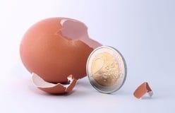 2欧元硬币离开破裂的被孵化的鸡蛋 免版税库存图片