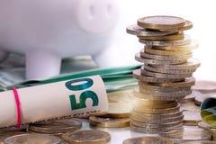 欧元钞票滚动了和欧元硬币用不同的位置 免版税库存照片